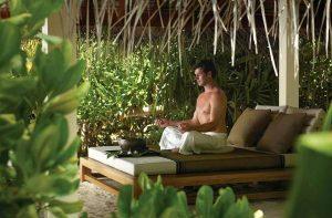 A man meditating at an yoga retreat and feeling relaxed.